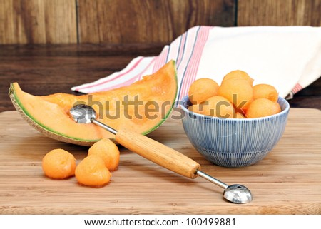 Cantaloupe melon balls in a bowl with selective focus.  Cantaloupe slice, melon baller and additional melons to the side. - stock photo