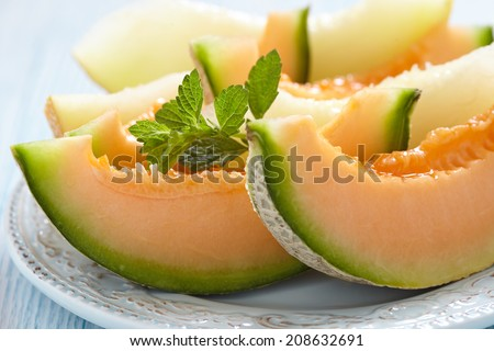 Cantaloupe melon slices on blue wooden table - stock photo