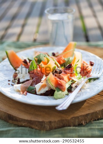 Cantaloupe salad with mozzarella and rucola - stock photo