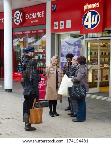 CANTERBURY, KENT, UK: JAN 31, 2014.  Ann Barnes, Kent's Police and Crime Commissioner talks to unknown members of the public during filming for a Channel 4 Documentary to be broadcast on May 29, 2014. - stock photo