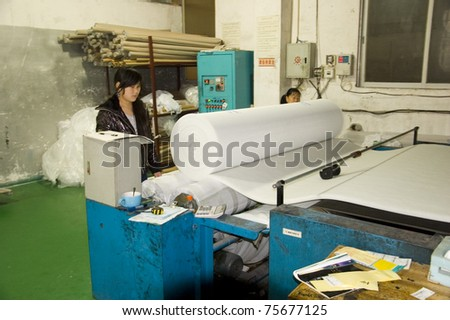 CANTON, CHINA - MARCH 9: Guangzhou air-filter factory produces all kinds of filters for spray booths, air conditioners, air purifiers etc. Two female operates folding machine on March 9, 2011 in Canton, China. - stock photo