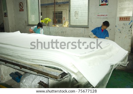 CANTON, CHINA - MARCH 9: Guangzhou air-filter factory produces all kinds of filters for spray booths, air conditioners, air purifiers etc. Two females cuts the edge of filter sheets on March 9, 2011 in Canton, China. - stock photo