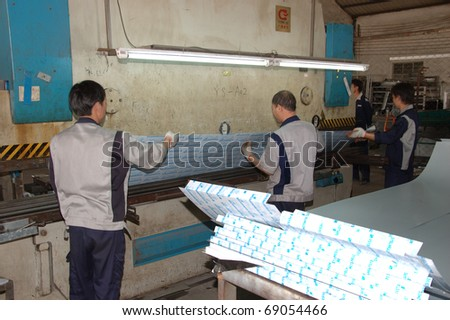 CANTON, CHINA - NOVEMBER 11: One of the biggest manufacturer of auto spray booths and generators in China. Chinese workers use machine to create aluminum profile on November 11, 2010 in Canton, China. - stock photo