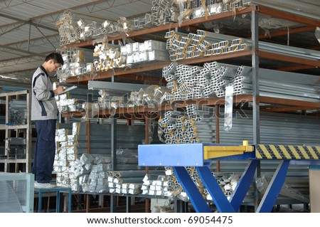 CANTON, CHINA - NOVEMBER 11: One of the biggest manufacturer of auto spray booths and generators in China. Warehouseman checks raw material on November 11, 2010 in Canton, China. - stock photo