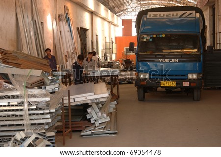 CANTON, CHINA - NOVEMBER 11: One of the biggest manufacturer of auto spray booths and generators in China. Workers unload truck with raw materials on November 11, 2010 in Canton, China. - stock photo