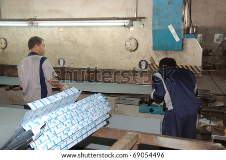 CANTON, CHINA - NOVEMBER 11: One of the biggest manufacturer of auto spray booths and generators in China. Workers with aluminum folding profiles machine on November 11, 2010 in Canton, China. - stock photo