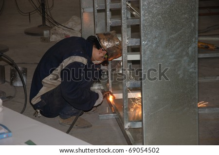 CANTON, CHINA - NOVEMBER 11: One of the biggest manufacturer of auto spray booths and generators in China. Welder working on aluminum frame on November 11, 2010 in Canton, China. - stock photo
