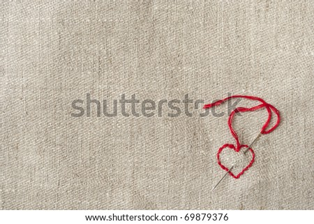 canvas background with an embroidered red heart - stock photo