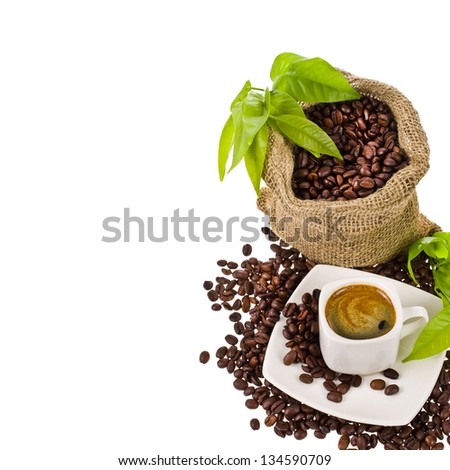 canvas bag with coffee beans decorated with green leaves and a cup of black coffee isolated on white background - stock photo