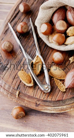 canvas bag with nuts in the shell on a wooden table, with tongs for cracking nuts