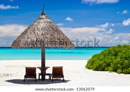 canvas chairs with parasol on a beautiful beach - stock photo