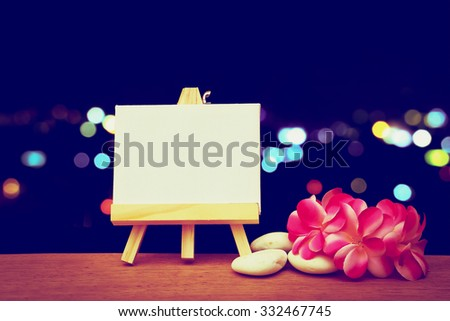 canvas frame and pink plumeria on  blur bokeh light in city background ,vintage tone - stock photo
