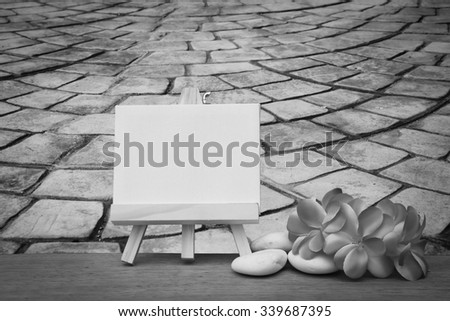 canvas frame and pink plumeria on blur perspective old stone floor - stock photo