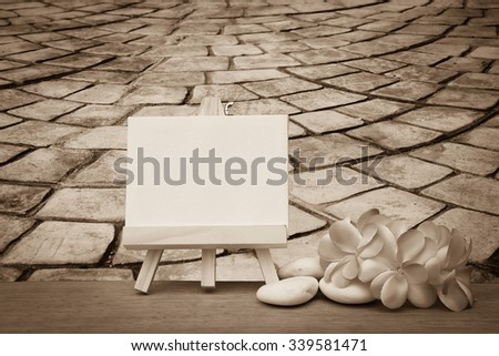 canvas frame and pink plumeria on blur perspective old stone floor ,vintage tone - stock photo