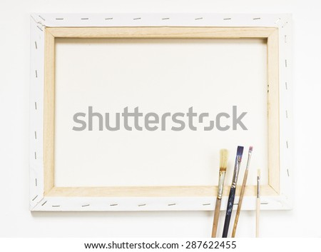 canvas frame with paint-brushes - stock photo