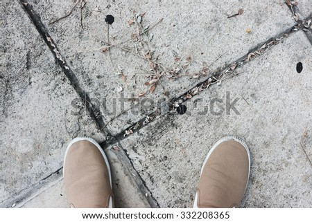 Canvas shoes on cements floor. - stock photo