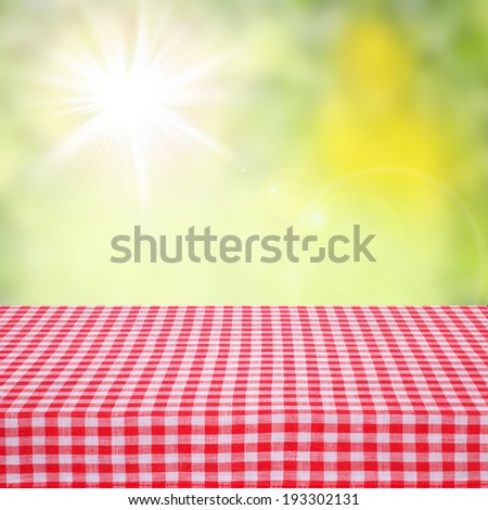 Canvas texture or background on table. Red checked tablecloth view from top. Empty tablecloth for product montage. Sunny summer day outdoors. Free space for your text  - stock photo