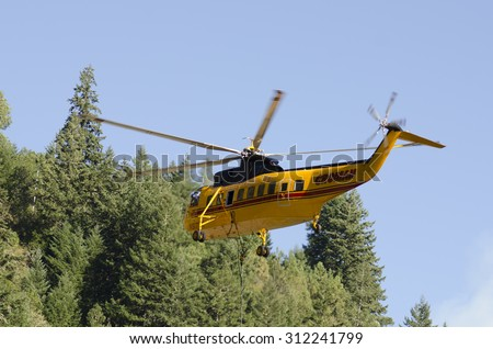 Canyonville, OR, USA - August 06, 2015: Sikorski, S-61, Type 1, helicopter comes in for a fill of its water bucket at a wildland fire in Oregon. - stock photo