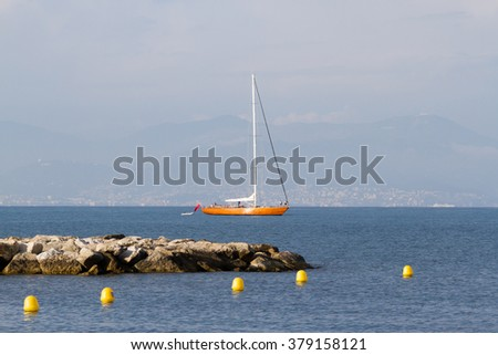 Cap d'Antibes - scenic sea-view with sailboat - stock photo