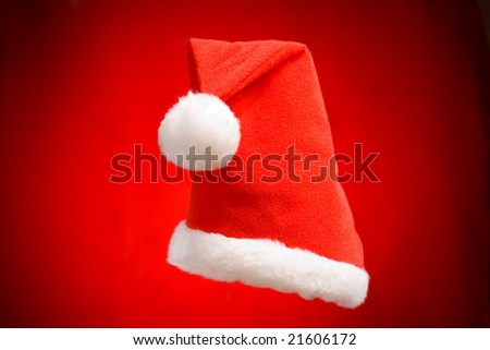 cap of Santa Claus ion the red background - stock photo