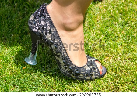 cap to put on the heels and not sink into the grass - stock photo