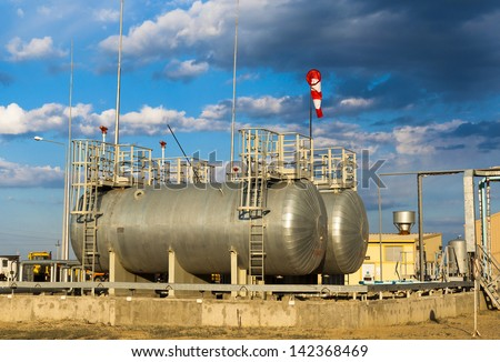 capacities for fuel on a production site against the cloudy sky - stock photo