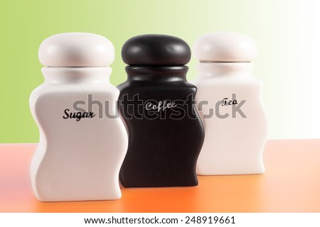 Capacities for sugar, coffee, tea on an orange surface and a green background. - stock photo
