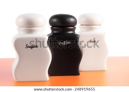 Capacities for sugar, coffee, tea on an orange surface and a white background. - stock photo