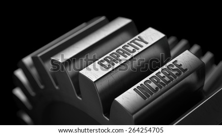 Capacity Increase on the Metal Gears on Black Background.  - stock photo