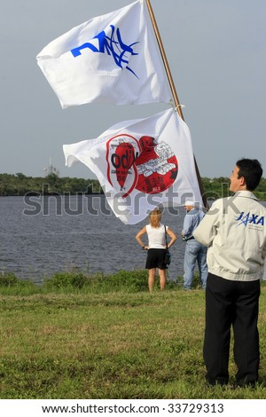 CAPE CANAVERAL, FL - JULY 15: A member of the Japanese Space Admin hoists a flag in honor of the Japanese Kibo module, launched by Space Shuttle Endeavour from Kennedy Space Center on July 15, 2009 in Cape Canaveral, FL. - stock photo
