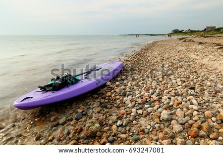 Cape Cod, Massachusetts - July 22, 2017: A purple kayak parking on the wood Neck Beach in Galmouth on Cape Cod. This warm water beach is found at the mouth of a saltwater lake.