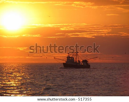 Cape Code fishing boat at sunset - stock photo
