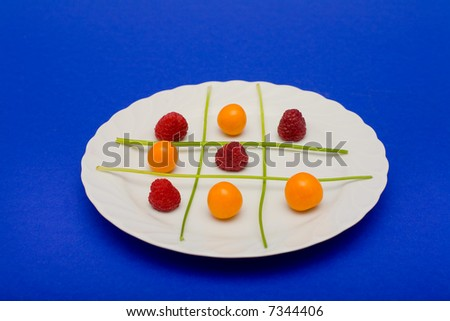 Cape gooseberries, raspberries and parsel arranged on a plate to look like a game of tic tac toe. - stock photo