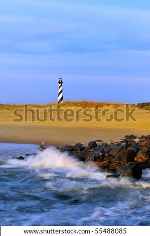 Cape Hatteras Lighthouse at Sunrise with Surf and Rocks - stock photo