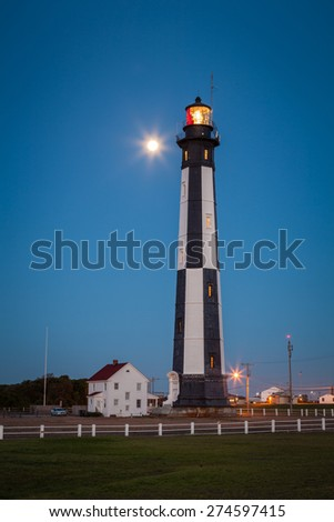 Cape Henry Lighthouse at dusk with full moon in background. This landmark is one of the oldest in the USA. It was built of cast iron in 1879 on Fort Story in Virginia Beach. / Cape Henry Lighthouse - stock photo