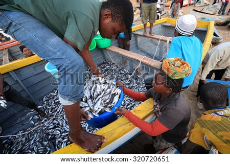 CAPE MACLEAR - MALAWI - AUGUST 6, 2015: Unidentified fishermen and market women trading fish on August 6, 2015 in the village Cape Maclear, Malawi - stock photo