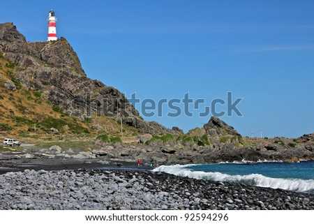 Cape Palliser Lighthouse above rock beach - stock photo