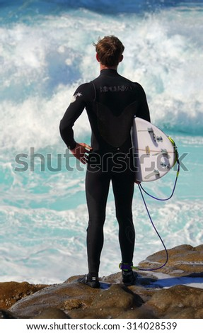 CAPE SOLANDER, AUSTRALIA - AUGUST -, 2015; Australian surfer stands and watches the wavesat Cape Solander.  He is wearing a RipCurl wetsuit and carrying his surfboard - stock photo