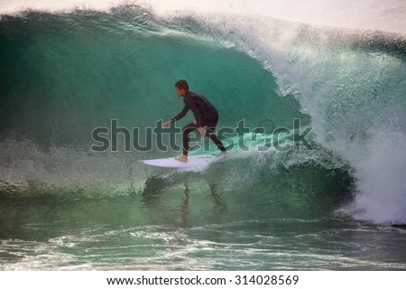 CAPE SOLANDER, AUSTRALIA - AUGUST 27, 2015; Surfer riding  a wave at Cape Solander  is a reef break and can be quite dangerous and in large swells only the best and bravest venture out - stock photo