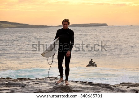 CAPE SOLANDER, AUSTRALIA - AUGUST 27, 2015; Surfer wearing full body wetsuit and carrying his surfboard, while a jetski waits to tow in another surfer or rescue those that get into trouble - stock photo