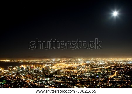 Cape Town harbor and city at night with moon in the sky - stock photo