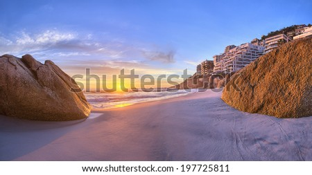 Cape Town's beautiful beaches including Clifton and Camps Bay at sunset with white sands and blue ocean water - stock photo