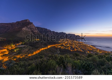 Cape Town's Table Mountain & Twelve Apostles seen from Lions Head hiking peak & Twelve Apostles with camps bay suburb and ocean below - stock photo