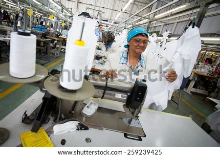 CAPE TOWN, SOUTH AFRICA - AUG 2: A woman creates a new garment in a large clothing factory in Cape Town, South Africa on August 2, 2012