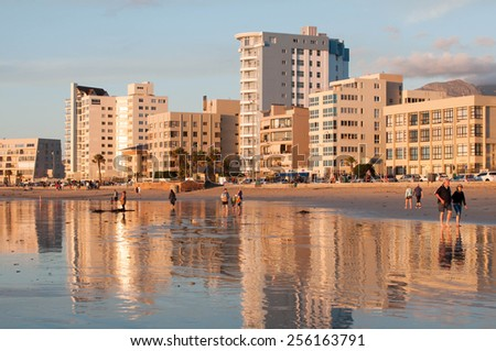 CAPE TOWN, SOUTH AFRICA - DECEMBER 20TH, 2014: Unidentified people on the beach at sunset in The Strand near Cape Town. It is a favorite tourists area