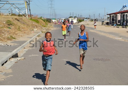 CAPE TOWN, SOUTH AFRICA - JANUARY 26, 2013: African children running towards you and smiling, in informal settlement Langa town ship - stock photo