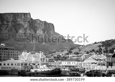 CAPE TOWN, SOUTH AFRICA - MAR 24: V&A waterfront harbor with fishing boats and Table Mountain in the background on March 24, 2015.  Table Mountain is one of the Seven Wonders of the Natural World. - stock photo