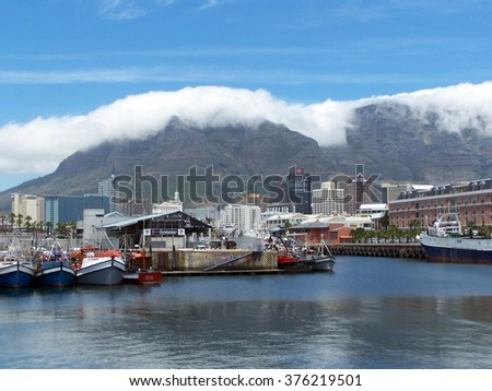 CAPE TOWN, SOUTH AFRICA - NOVEMBER 9, 2006: Harbor at the Victoria and Alfred Waterfront with moored fishing boats and Table Mountain in the background, with clouds hovering at the top