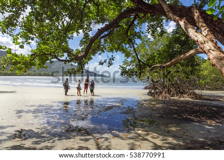 CAPE TRIBULATION - AUSTRALIA - CIRCA 2016 - Tourists walk carefully on a beach in the Daintree World Heritage area, known for crocodiles and box jellyfish.