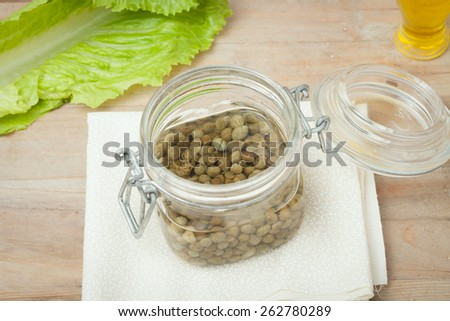 capers in glass jar on wooden background - stock photo